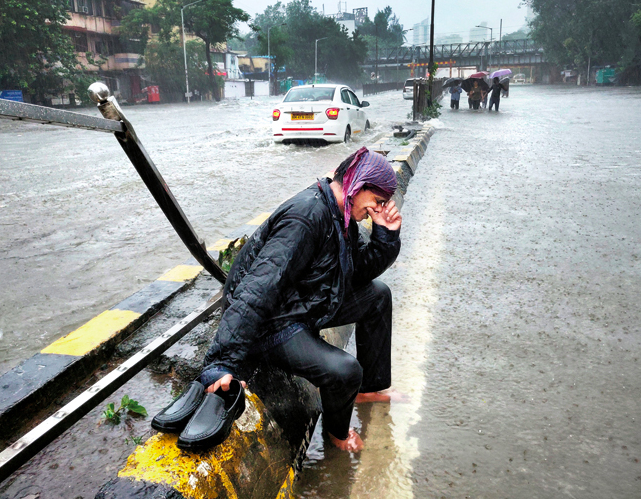 A man cries while sitting on the divider of a water-logged street of Mumbai and the rain keeps pouring
