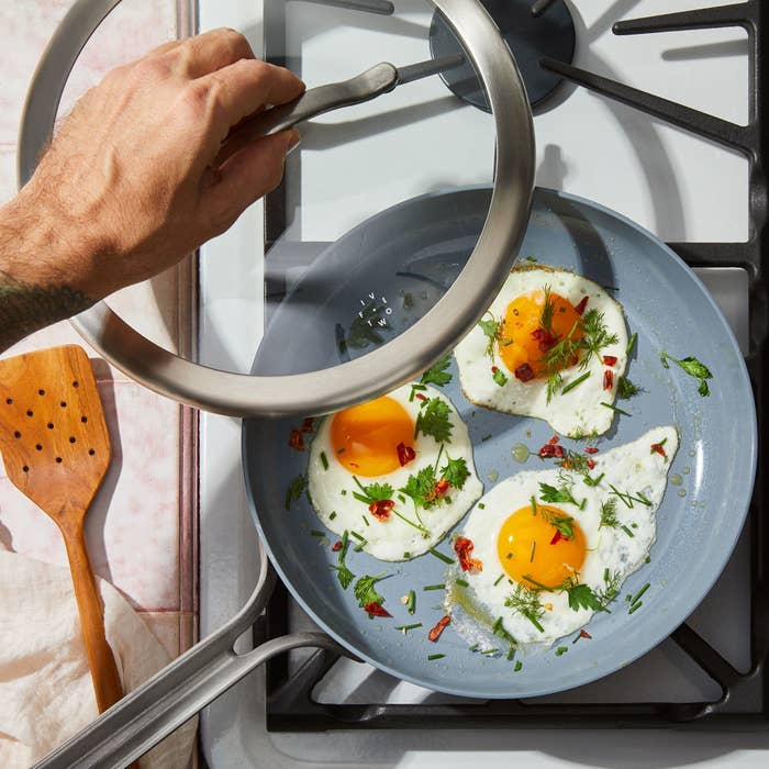 Three eggs frying in a non-stick skillet with a lid on the stove top.