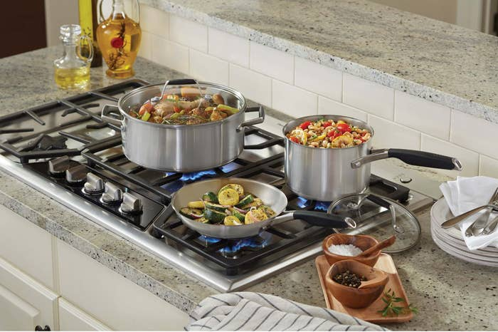 A frying pan and two different sized sauce pans full of food cooking on the stovetop.