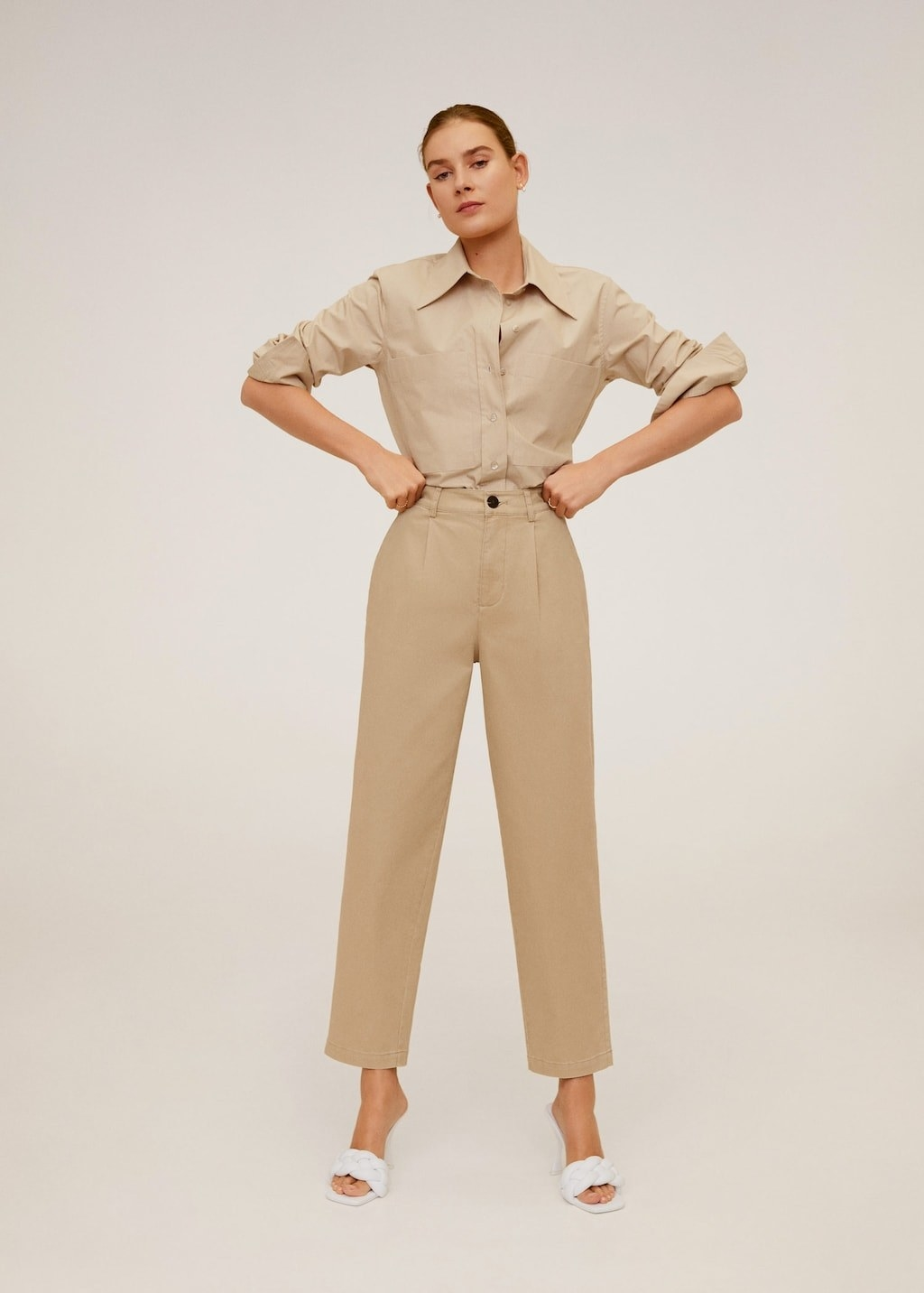 Model wearing trousers in a khaki color that hit at the ankles