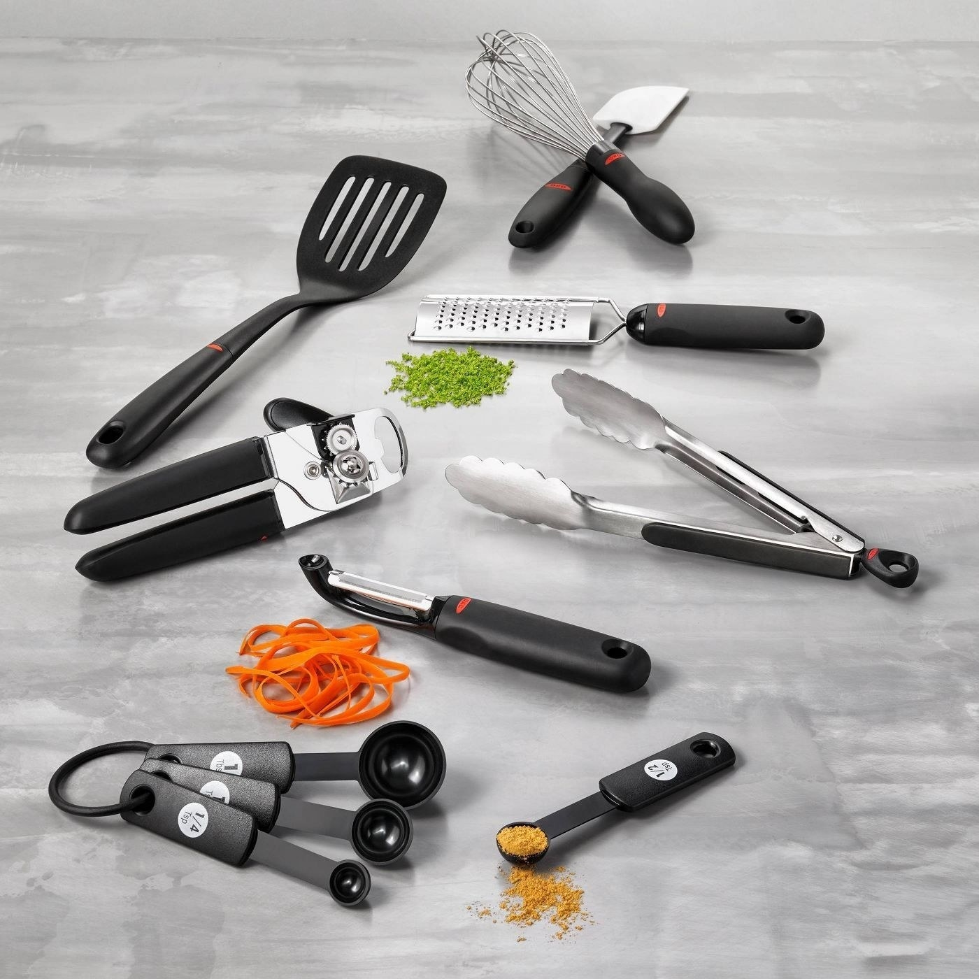 A set of OXO cooking tools like measuring spoons, can opener, tongs, microplane grater, whisk, and spatula.