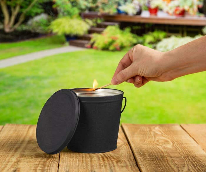 Model's hand lighting citronella candle in a black container