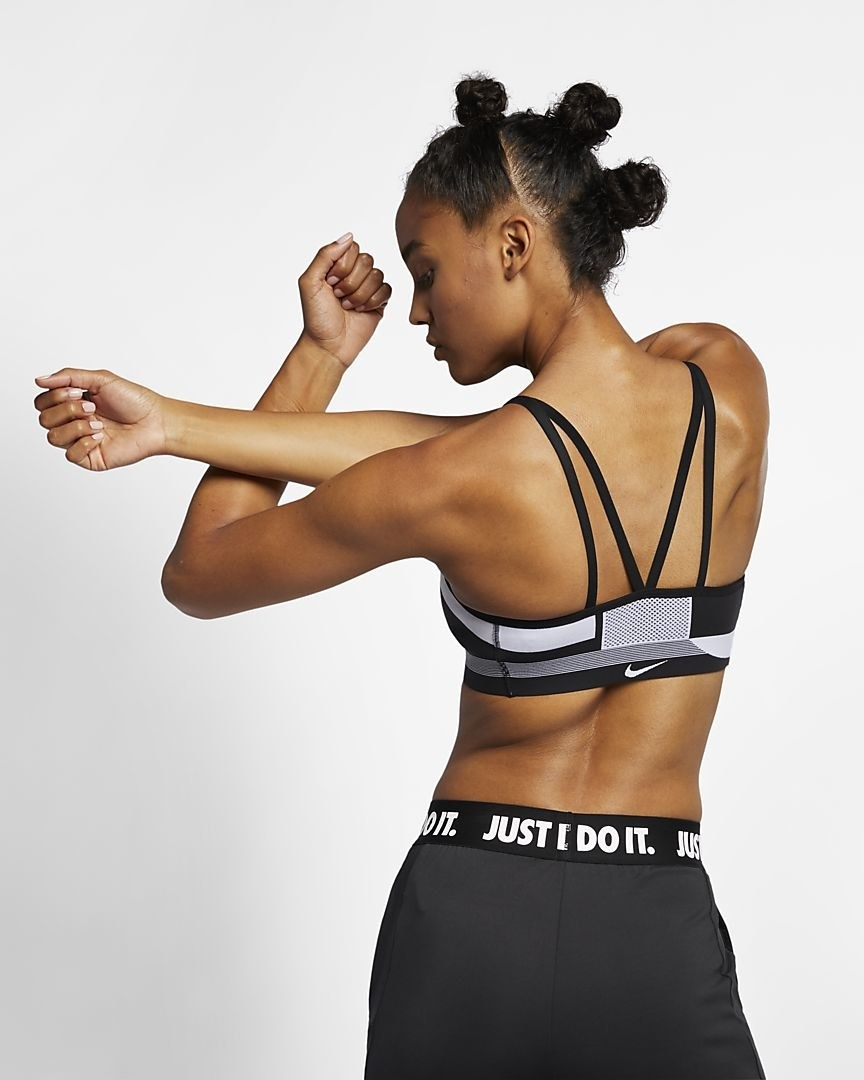Model wearing the black and white bra as seeon from the back, with four v straps for support