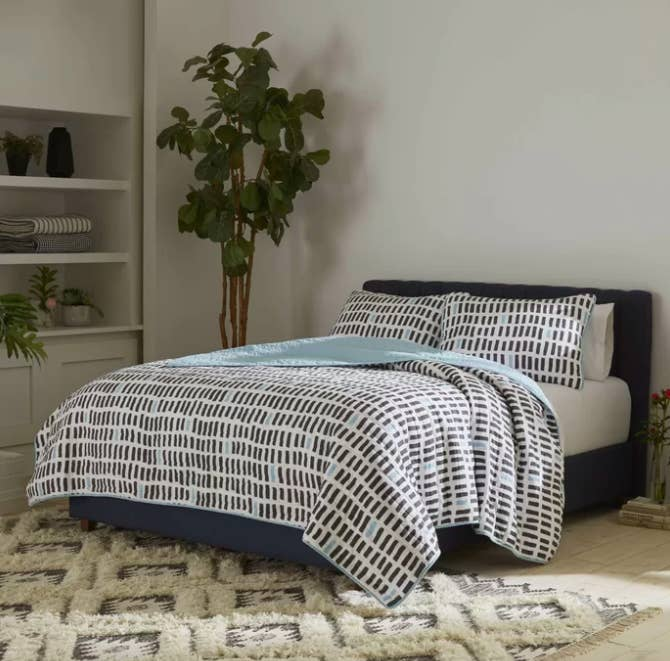 Baby blue geometric-print reversible quilt with matching pillow shams and white sheets