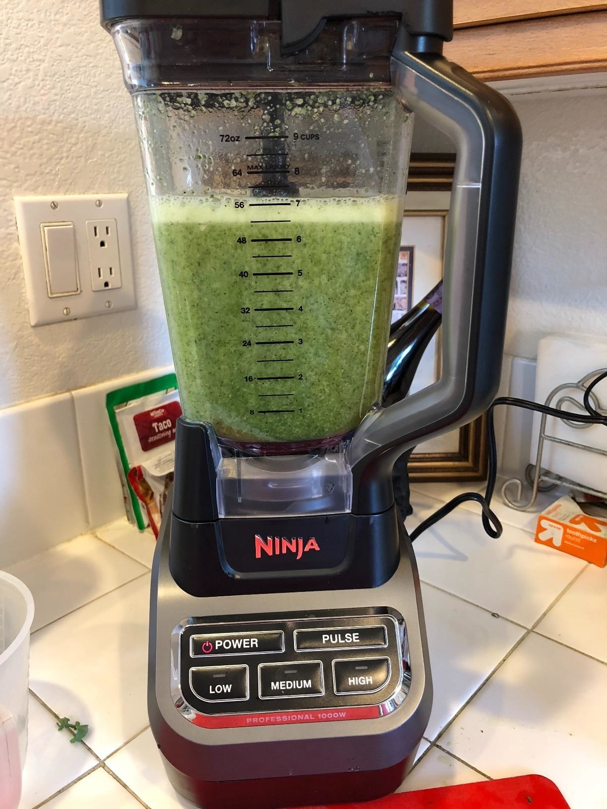 A Ninja blender with a green smoothie in the jar.