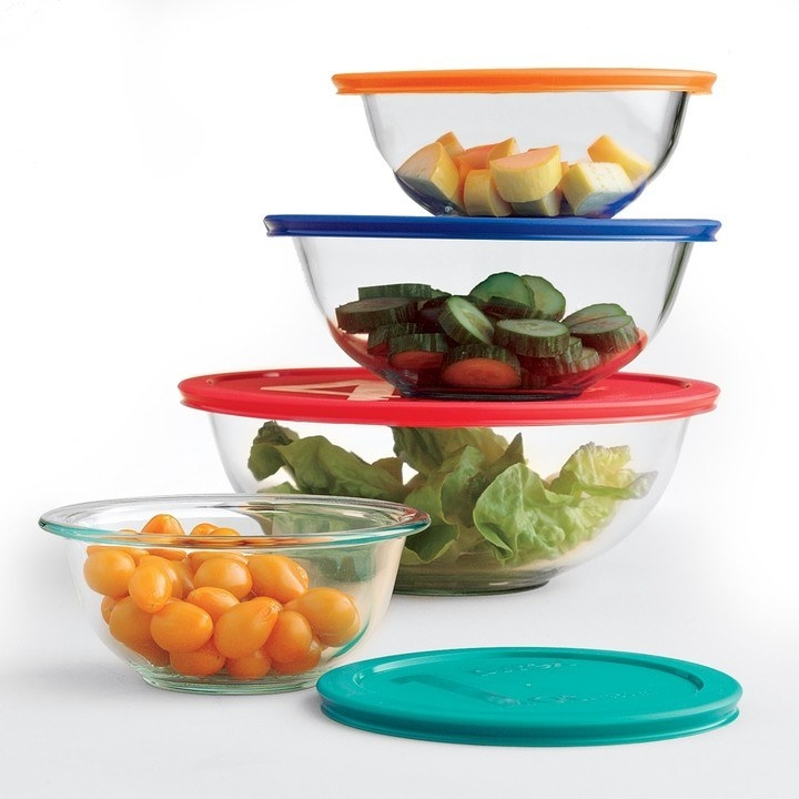 Four glass mixing bowls with colorful lids filled with different chopped veggies.