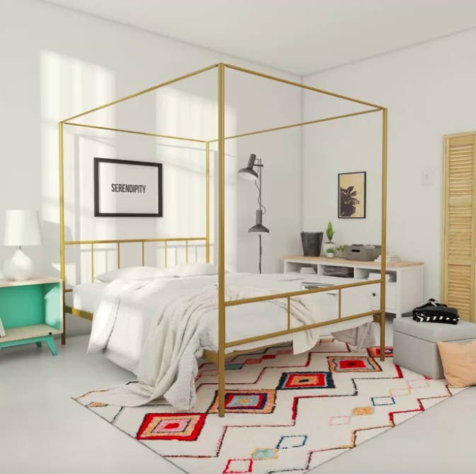 Gold-colored canopy bed with white sheets on top of a rainbow geometric woven rug