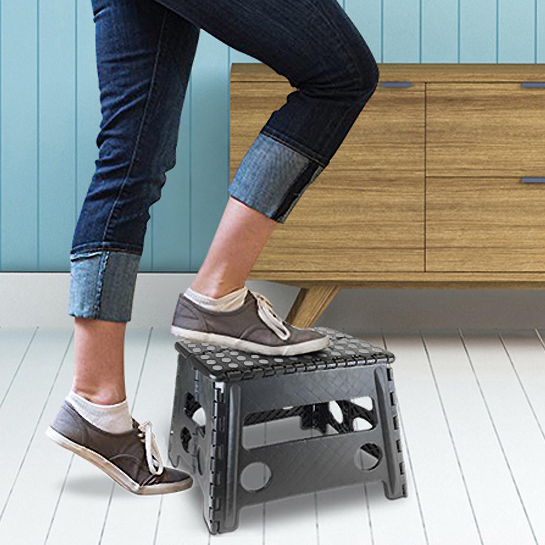 Model using black plastic step stool