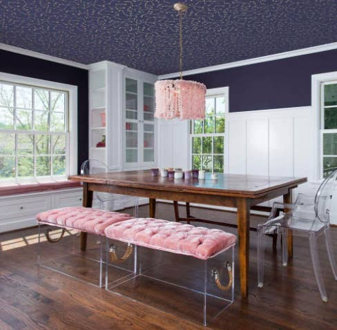 Navy blue removable wallpaper with a constellation print above a wood dining table and plush velvet benches