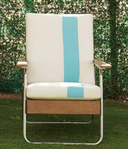 White patio chair with a turquoise stripe on the side on a grassy balcony
