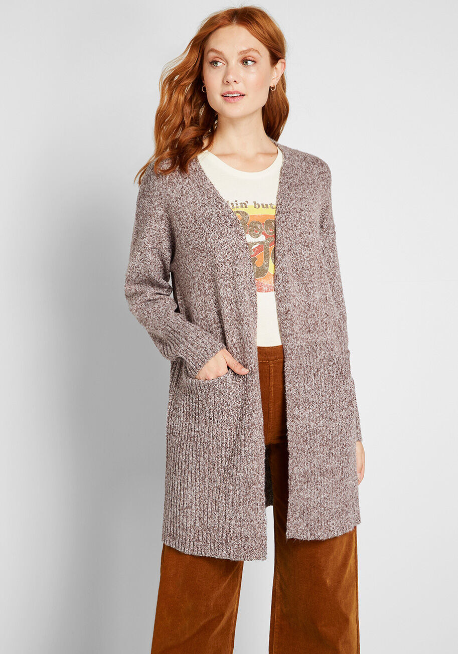 A brown and cream knit cardigan that falls mid-thigh and has front pockets