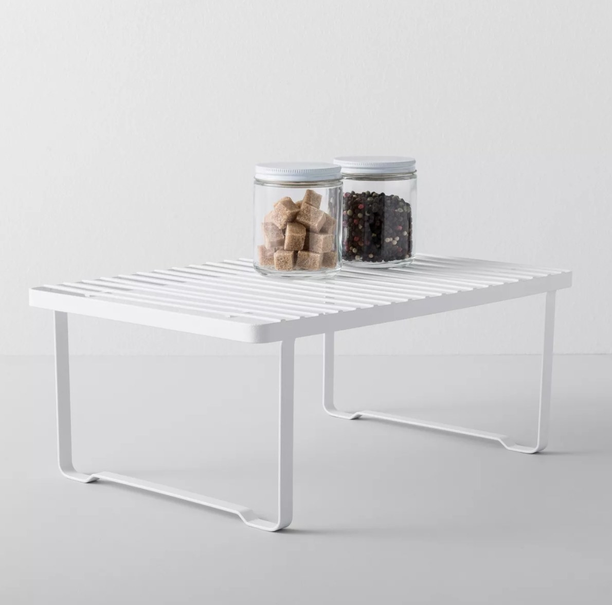 White riser shelf with two jars on top of it