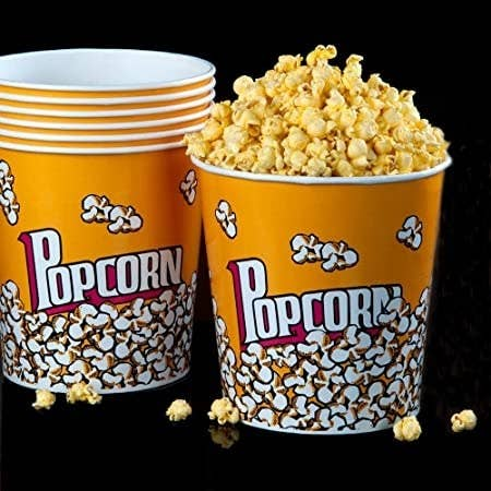 Popcorn holders stacked in each other and one overflowing with popcorn