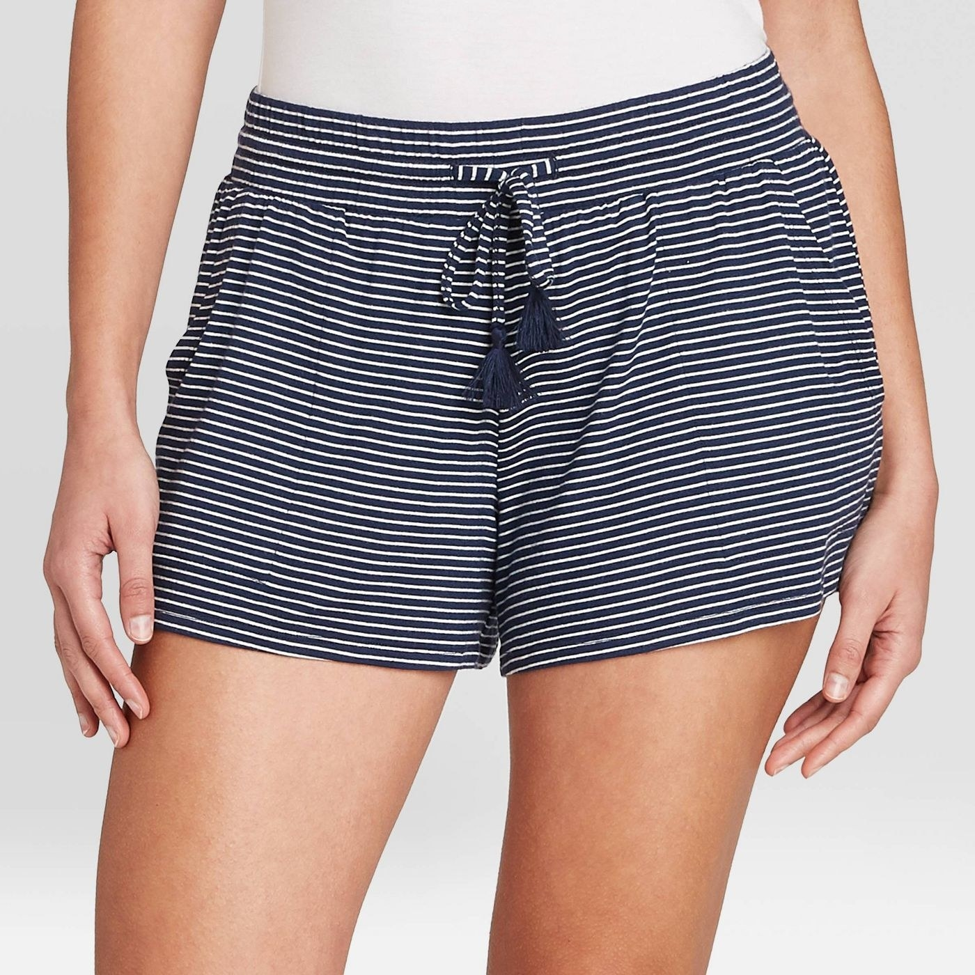 model wearing navy and white striped shorts