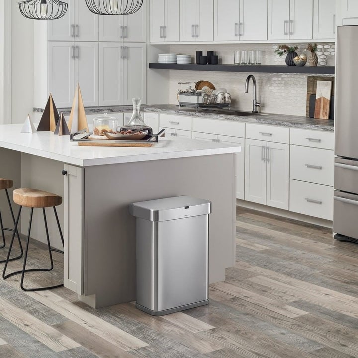 a stainless steel simplehuman garbage can in a nice clean kitchen