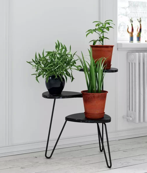 A black three-tier plant stand with assorted tan and black-glazed plant pots