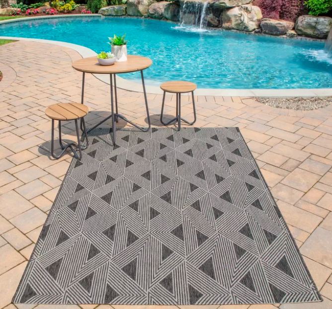 Rectangle black and gray power loom rug in front of a squiggly patio table and chair set and a blue pool
