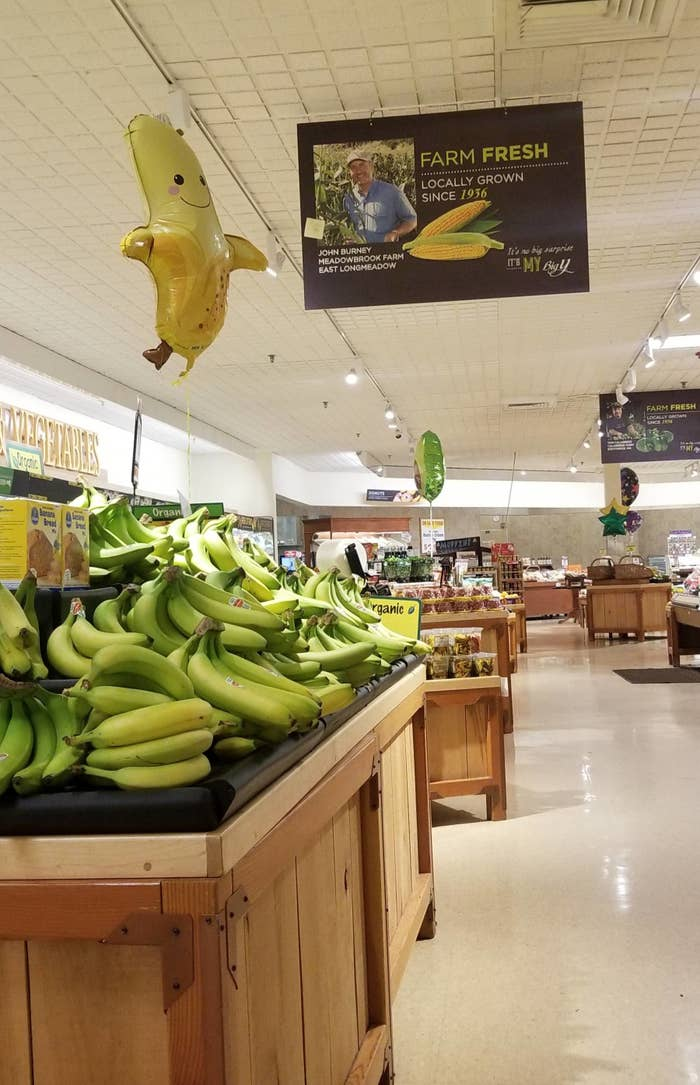 A produce section of a grocery store with a banana balloon above the bananas.