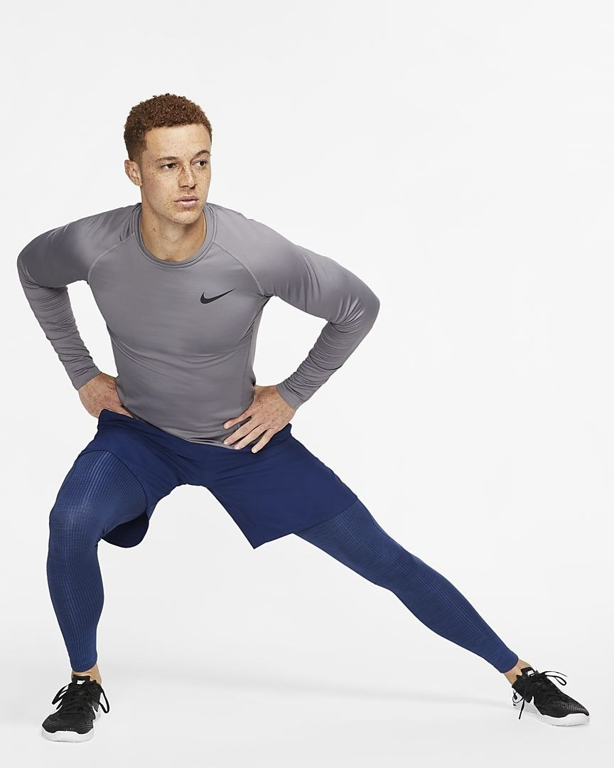 Model doing a side-lunge in the tights in blue, worn under a pair of shorts