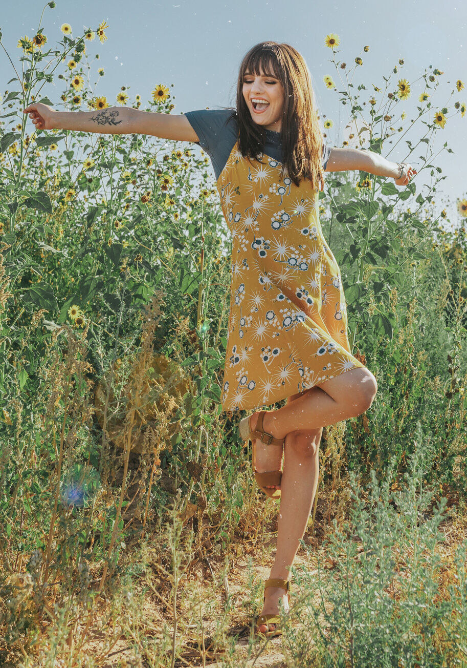 A model wearing the dress in the yellow floral pattern. It is paired with a gray T-shirt underneath.