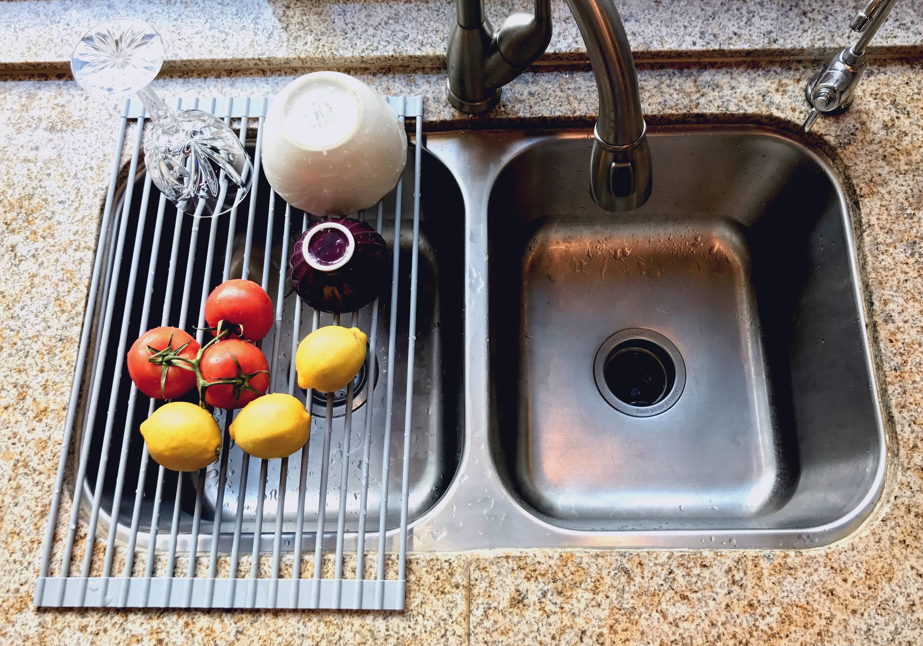 A grated gray drying rack over a sink