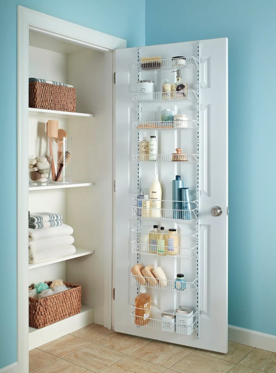 A white wire frame over-the-door rack with bath products in it