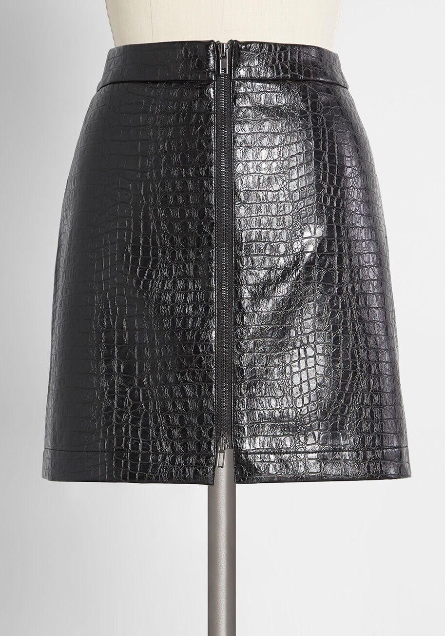 A high-waisted black mini skirt in a crocodile faux leather with a black zipper in the center that goes from the top to the bottom