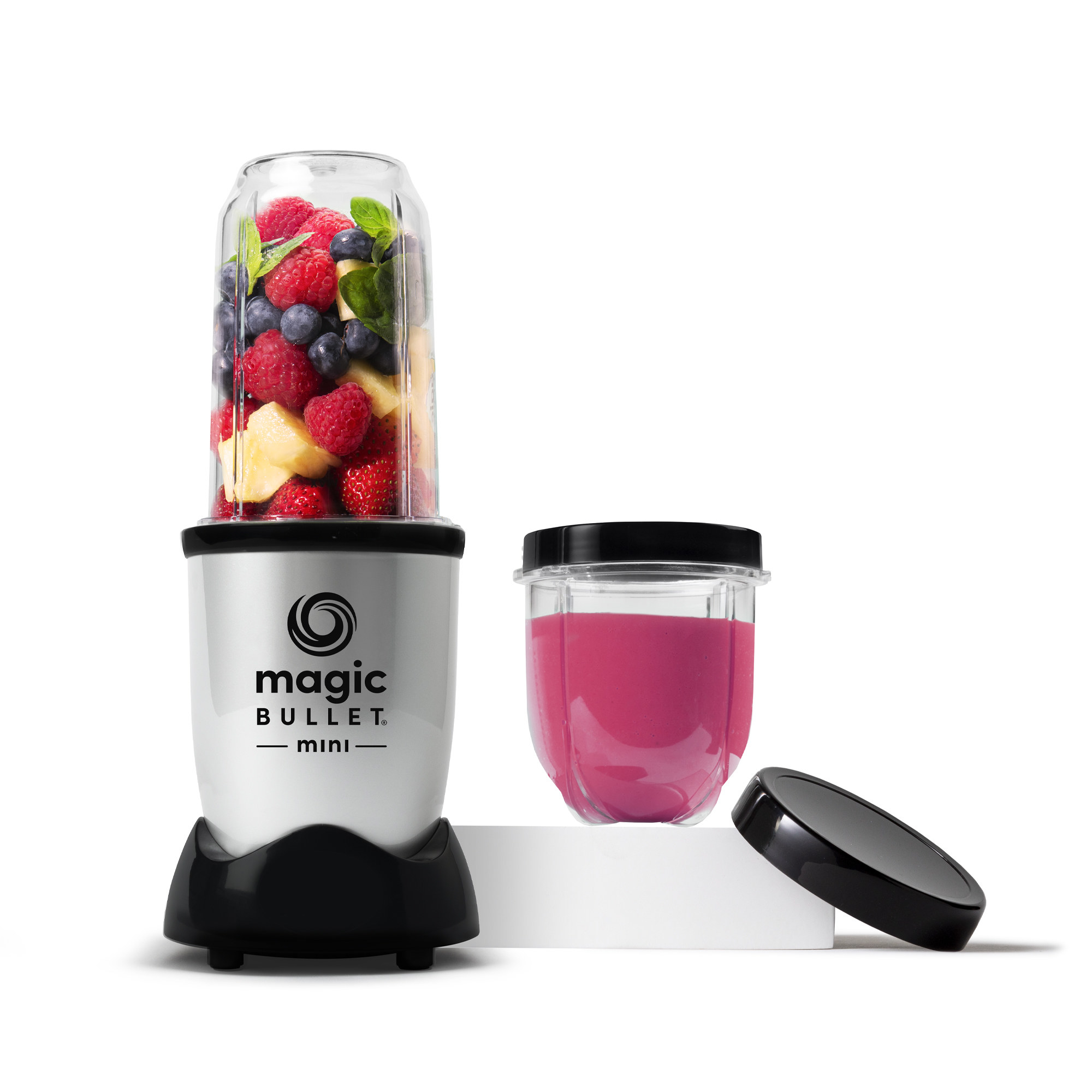 A silver blender with a black base and clear plastic cup filled with fruit next to a smoothie