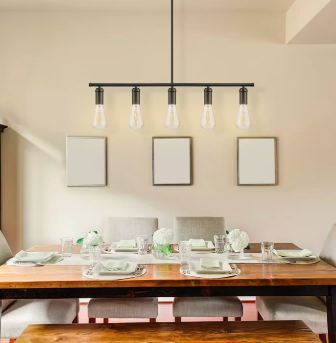 Five-bulb hanging light pendant above a wooden dining room table lined with green and neutral silverware