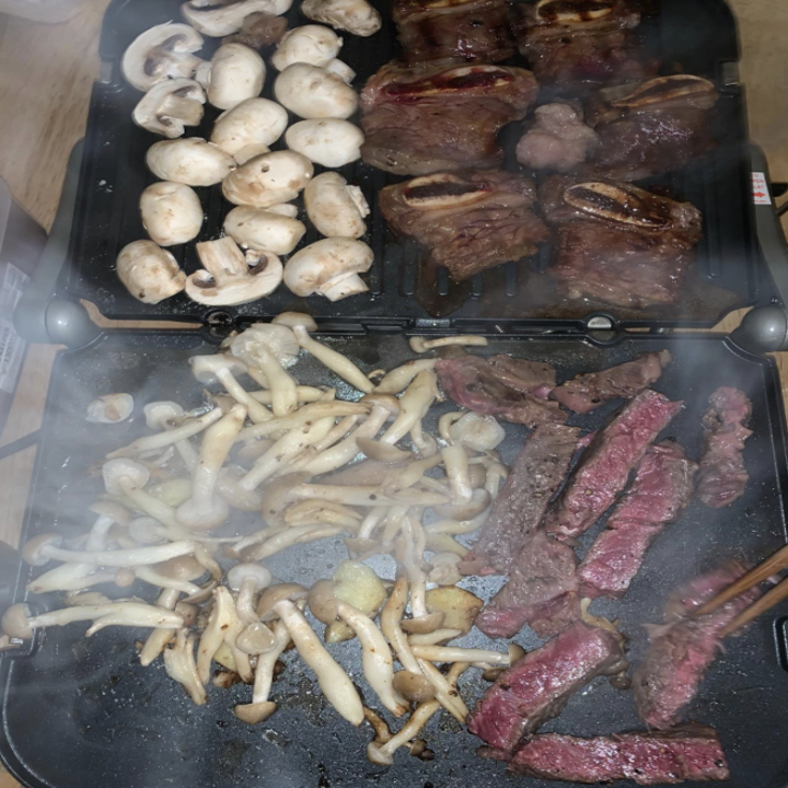 a reviewer photo showing the griddler fully open and cooking veggies, meat, and potatoes on it all at once