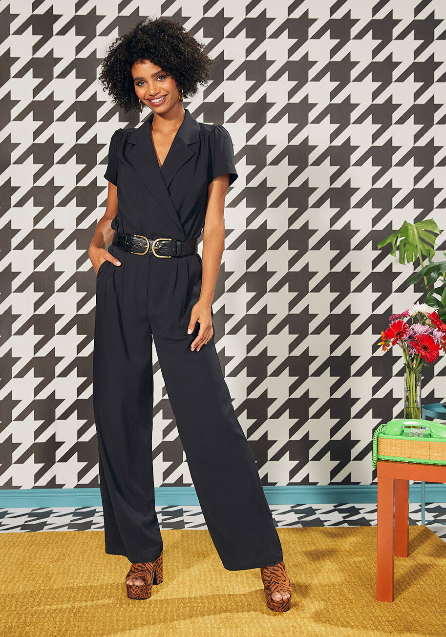 A jumpsuit in black with long loose fitting pant legs, front pockets, short puckered sleeves, and an asymmetrical twist top half with a V-neck collar