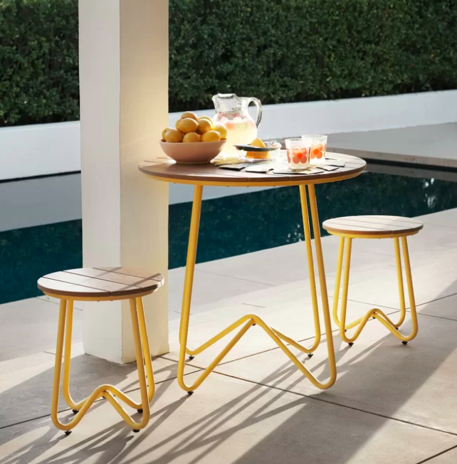 Yellow squiggly outdoor dining set with a tall table and two small stools