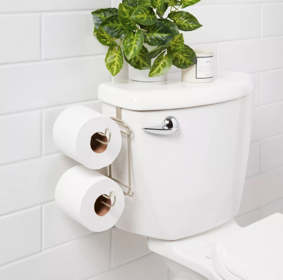 A metal two-roll toilet paper holder hooked onto the tank of a toilet