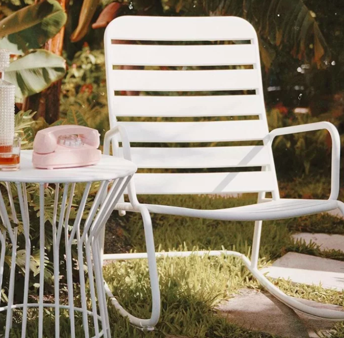 White outdoor rocking chair next to a white table with a retro-design pink phone and glass vase