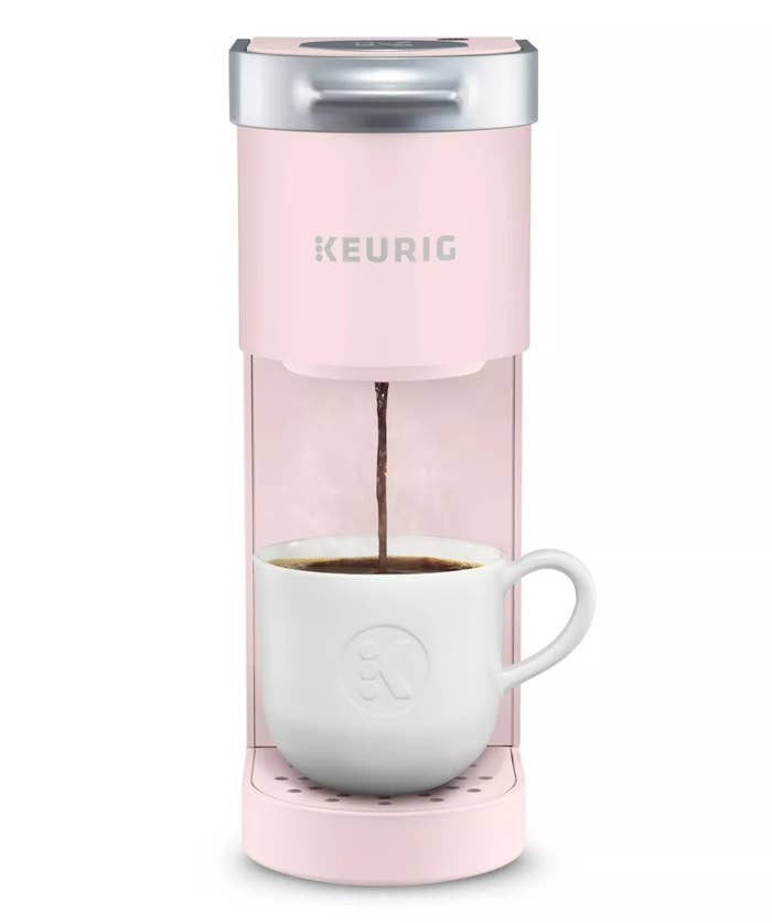 Pale pink Keurig K Mini coffee maker pouring a cup of coffee