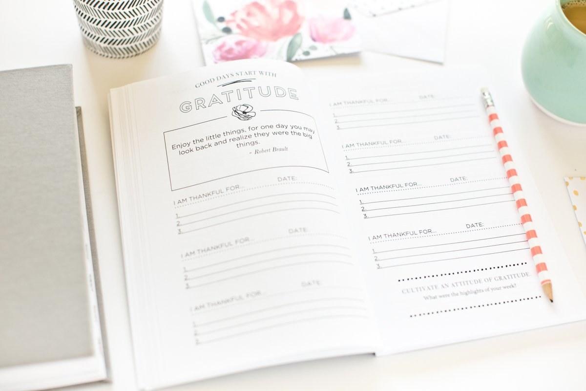 An open gratitude activity journal on a desk
