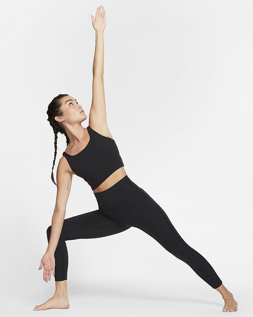 Model doing a yoga pose in the high waist black leggings