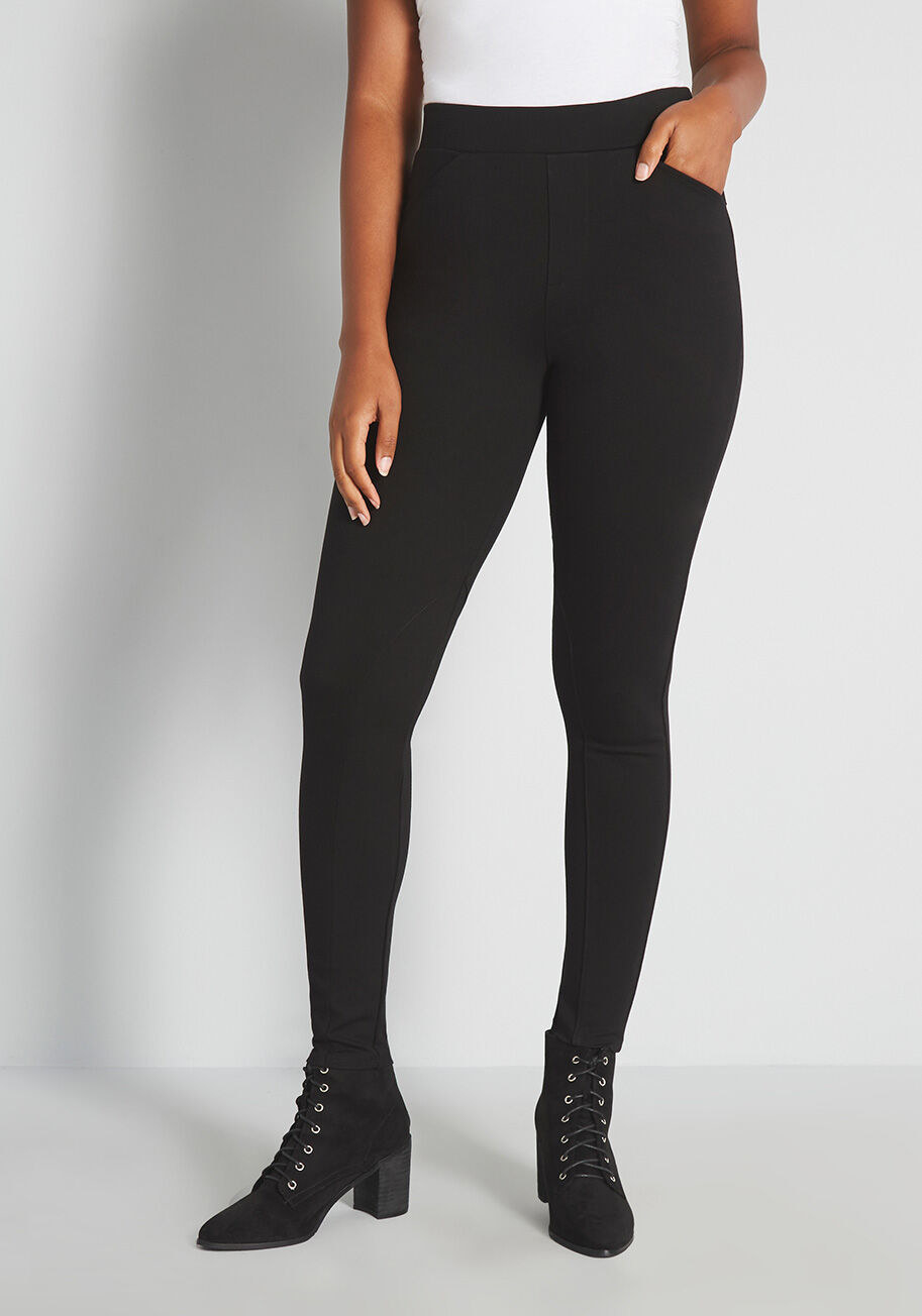 Long black leggings that hits just above the natural waist and has two thin pockets in the front