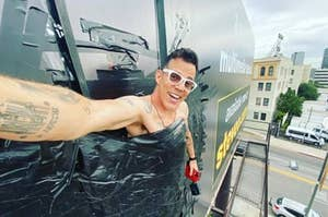 Steve-O duct taped to a billboard