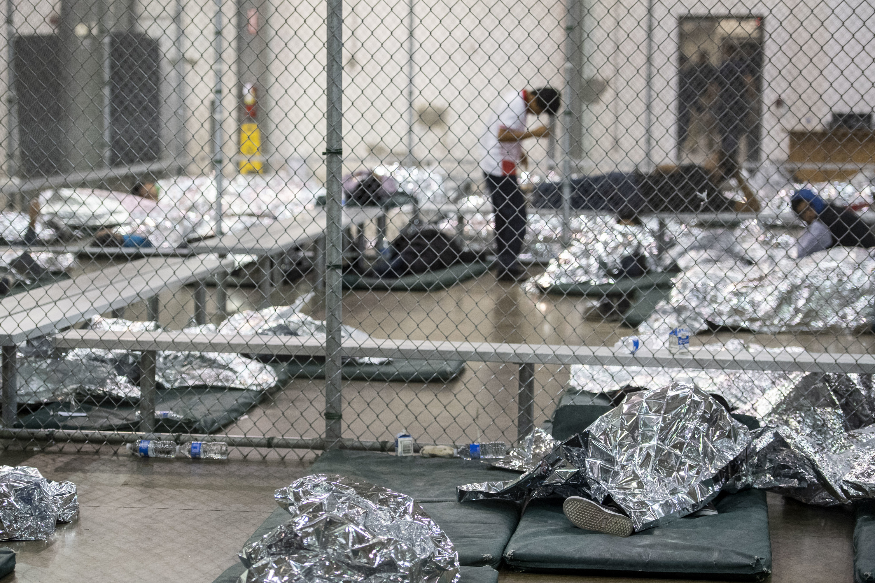 The children lie on padded mats on the floor, in groups separated by wire fencing.