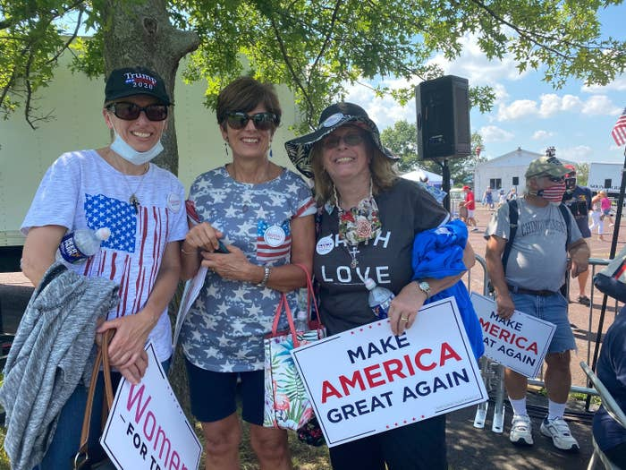 """Three white women, two without face masks and one with hers on her chin, hold """"Make America Great Again"""" and """"Women for Trump"""" signs."""