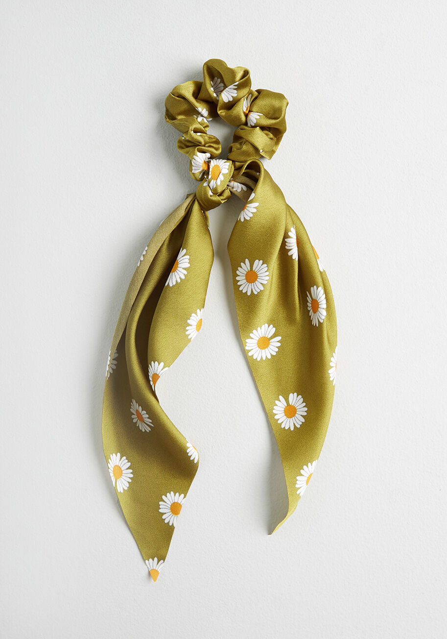 An olive green scrunchie with daisy print. It has two long ribbons on either side.