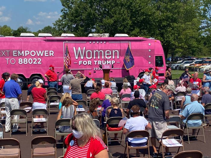 """A huge bus painted with """"Women for Trump 2020"""" and other slogans is parked in front of rows of folding chairs occupied by men and women, many of whom are wearing face masks."""