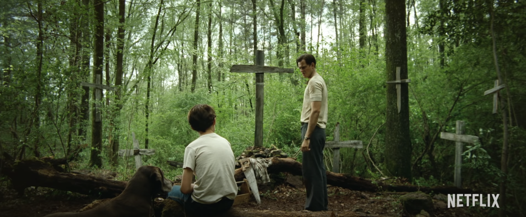 "Arvin (Tom Holland) and Willard (Bill Skarsgård) in a creepy forest, surrounded by crosses, in ""The Devil All The Time."""
