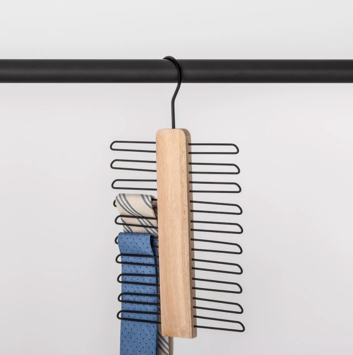 A wooden and metal tie hanger with two ties