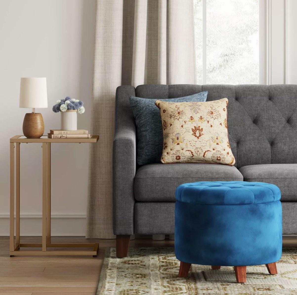 Blue velvet ottoman with wooden legs in living room scene