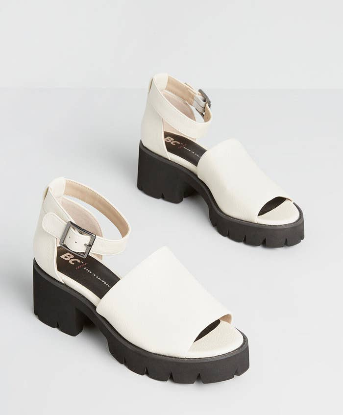 White sandals with chunky black soles, peak toes, and ankle straps with silver buckles