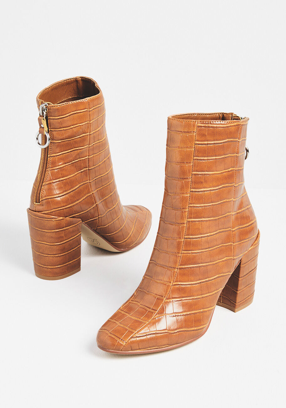 A faux crocodile leather boot in tan with high heels and a zipper detail