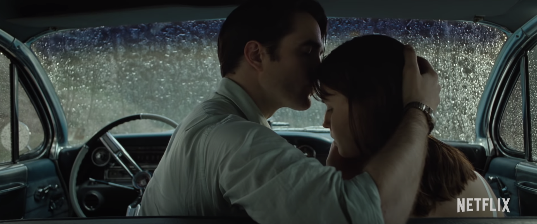 "Rev. Teagardin (Robert Pattinson) kissing Leonora's (Eliza Scanlen) forehead in the front seat of his car while it rains outside in ""The Devil All The Time."""