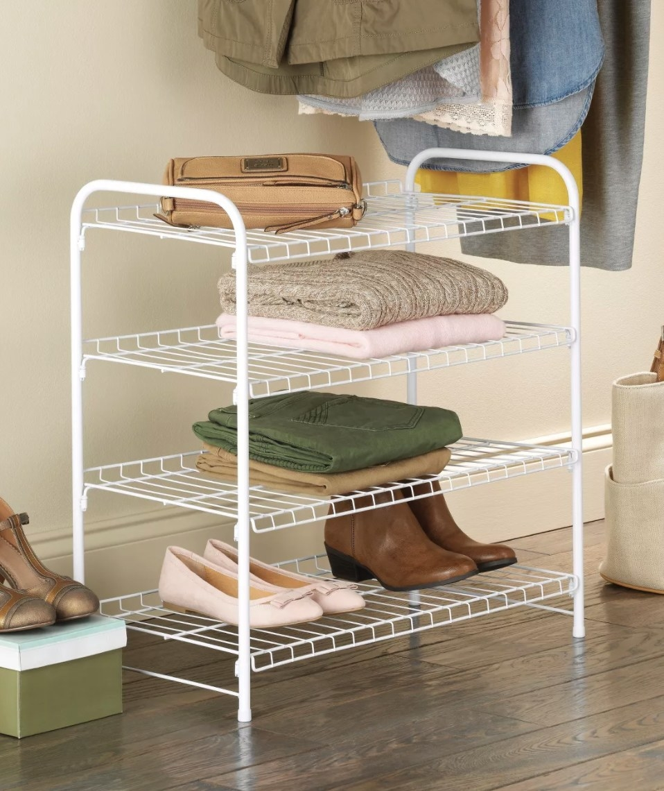 A four-tier white wire frame shelf with shoes, pants, sweaters, and a purse on it